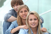 Three students sitting in line — Stock Photo