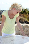 Blond woman looking at old stone map — Stock Photo