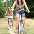 Two teenage girls on bikes in the forest — Stock Photo