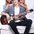 Teenagers playing a guitar in a white bedroom — Stock Photo