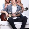 Foto de Stock  : Teenagers playing guitar in white bedroom
