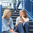 Foto Stock: School girls talking on steps