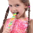 Stock Photo: Little girl with plaits sucking lollipop