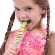 Little girl with plaits sucking lollipop — Stock Photo