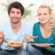 Couple having dinner on the couch — Stock Photo