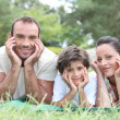 Happy family lying on the grass - Foto Stock
