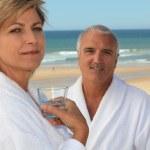 Couple on a beach in bathrobes — Stock Photo