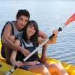Young man and woman doing canoe on a lake — Stock Photo #7391933