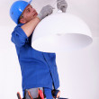 Electrician fitting a ceiling light — Stock Photo #7392183
