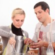 Husband and wife whisking mixture — Stock Photo