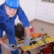 Young plumber with miscellaneous tools - Stock Photo