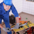 Stock Photo: Young plumber with miscellaneous tools