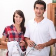 Stock Photo: Young couple wiping glasses in kitchen