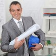 Architect with plans and hardhat — Stock Photo