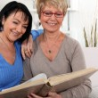 Royalty-Free Stock Photo: Two senior friends looking at a photo album