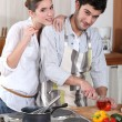 Portrait of young man cooking in kitchen with girlfriend — Stock Photo