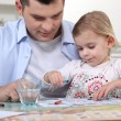 Young girl coloring with dad — Stock Photo #7394684