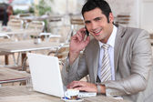 Businessman working in a cafe — Stock Photo