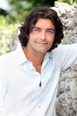 Handsome man with long hair standing by an old stone wall — Stock Photo