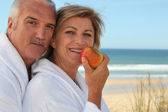 Mature couple in bathrobes eating an apple on the beach — Stock Photo