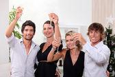 Due giovani coppie, bere champagne a natale — Foto Stock