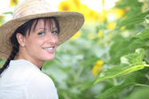 Woman in a straw hat in a sunflower field — Stock Photo