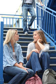 School girls talking on steps — Stock Photo