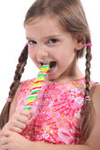 Little girl with plaits sucking lollipop — Stock Photo