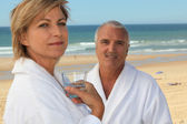 Couple on a beach in bathrobes — Stock Photo
