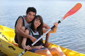 Young man and woman doing canoe on a lake — Stock Photo