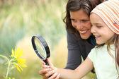 Anne ve kızı bir çiçek bir büyüteç kullanarak incelenmesi — Stok fotoğraf