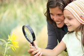 Mother and daughter examining a flower using a magnifying glass — Stok fotoğraf