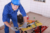 Young plumber with miscellaneous tools — Stock Photo