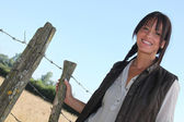 Female farmer stood by barb-wire — Stock Photo
