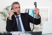 Businessman on two telephone calls — Stock Photo