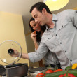 Stock Photo: Couple cooking in a kitchen