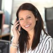 Stock Photo: Smiling woman with a telephone headset