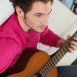 Young man playing his guitar at home — Stock Photo #7414915