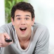 Dumbfounded man watching TV — Stock Photo