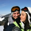 Young couple on a ski slope - Stock Photo
