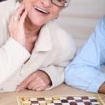 笑っている老婦人は誰かとチェッカーを再生 — ストック写真