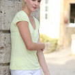 Pretty blond womanstanding in front of her house — Stock Photo