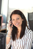 улыбающиеся женщина с гарнитуры телефон — Стоковое фото