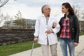 Kvinnan promenader med en äldre dam — Stockfoto