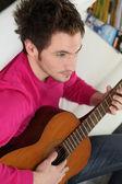Jeune homme jouant de sa guitare à la maison — Photo