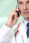 Serious doctor using a cellphone — Stock Photo
