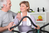 Older couple working out in a gym — Stock Photo