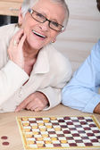 An old laughing lady playing checkers with somebody. — Stock Photo