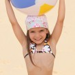 Little at the beach holding inflatable ball above head — Stock Photo