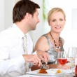 Couple sat at table eating meal and drinking wine — Stock Photo #7421957
